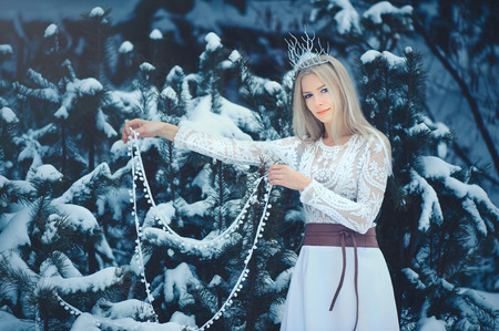 Winter Beauty Woman. Beautiful fashion model girl with snow hairstyle and makeup in the winter forest