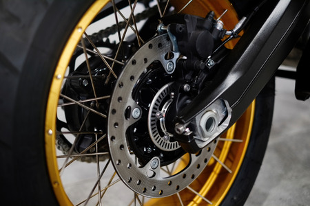 Disc brake with wheel hub on a motorcycle. Close up rear disc brake on a motorcycle.