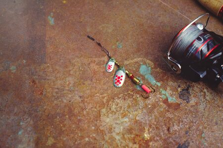 Fishing tackle - fishing spinning, hooks and lures on a darken rust Banco de Imagens
