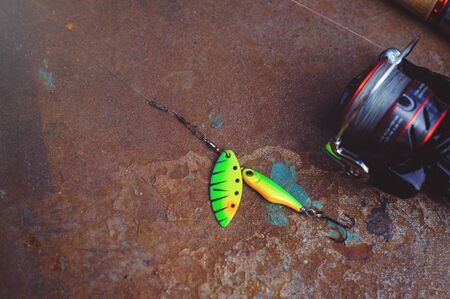Fishing tackle - fishing spinning, hooks and lures on a darken rust Imagens