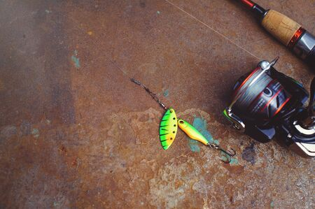 Fishing tackle - fishing spinning, hooks and lures on a darken rust