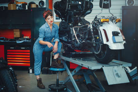beautiful girl repairs a motorcycle in a workshop, pin-up style, service and sale.