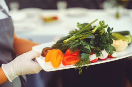 Fresh vegetable salad with radishes, cucumbers, bell peppers, tomatoes and herbs in a ceramic bowl in the hands of a waiter. Selective focus.