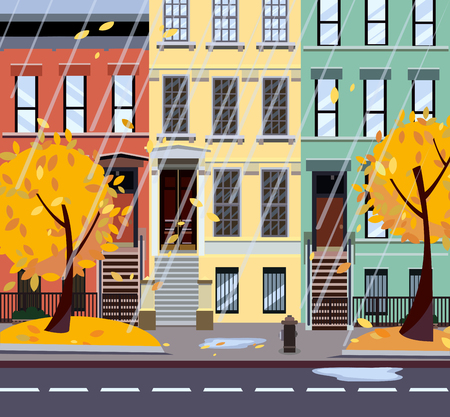 Flat cartoon vector illustration of autumn rainy city street. Three-four-story uneven colorful houses, foliage. Street cityscape. Evening city landscape with autumn trees in the foreground, puddles