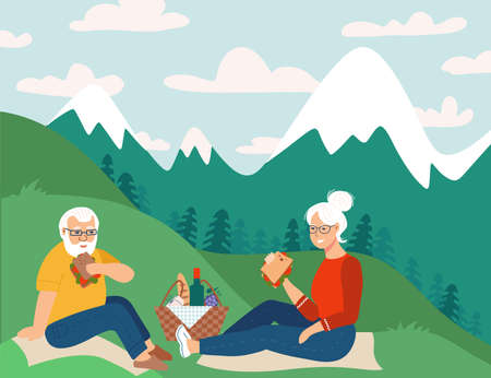 Cheerful senior couple having picnic in mountains, sitting on grass.