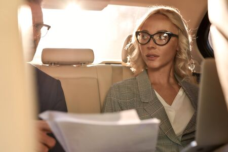 Listening carefully. Young and beautiful woman in eyeglasses looking at her business partner and discussing contract conditions while sitting in the car