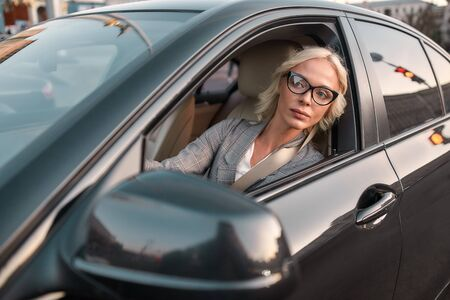 Why so slowly. Portrait of young caucasian business woman in classic wear looking in the window while sitting behind the wheel of a black car