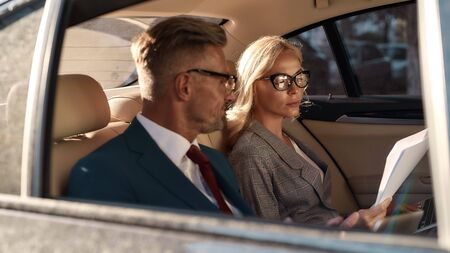 Checking information. Young and beautiful woman in eyeglasses reading documents while sitting with her business partner in the car. Business concept. Success. Partnership