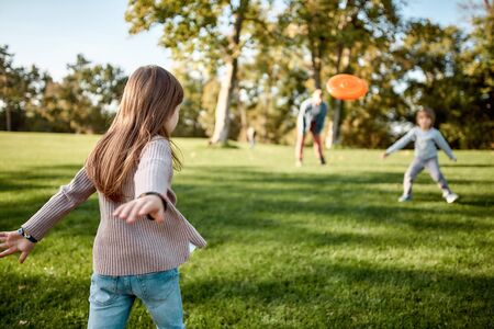 Here we go again. Little girl playing disk with her family in the park on a sunny day Standard-Bild