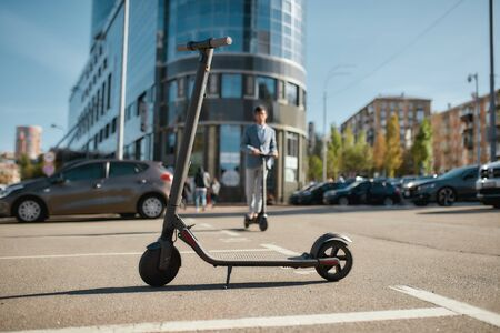 Horizontal shot of black electric scooter for adults standing outdoors on city street. Man is riding a scooter in the background. Modern technology, land vehicle, alternative transport concept.