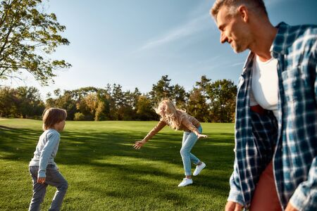 Growing together. Excited family running outdoors on a sunny day 写真素材