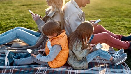 Technologies. Family spending time in the park on a sunny day 写真素材