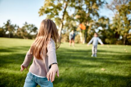There is no better gift than a family. Little girl playing flying disk with her family in the park on a sunny day Archivio Fotografico - 140878681