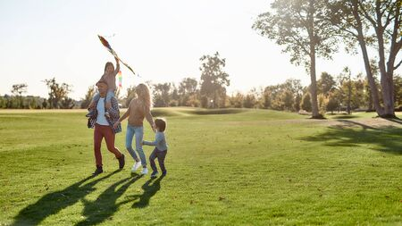 Full-length portrait of cheerful parents with two kids running with kite in the park on a sunny day. Family, kids and nature concept. Horizontal shot. Banco de Imagens
