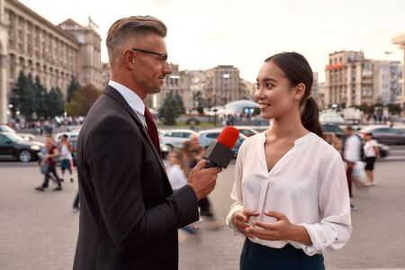 Its time to get connected. Professional reporter interviewing woman on urban street. Journalism industry, live streaming concept