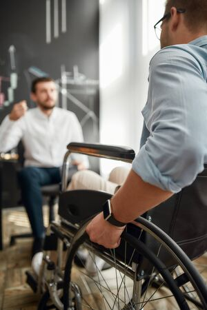 Cropped photo of office worker in a wheelchair discussing something with his male colleague while working together in the modern office. Teamwork. Disability and handicap concept. Business meeting Zdjęcie Seryjne