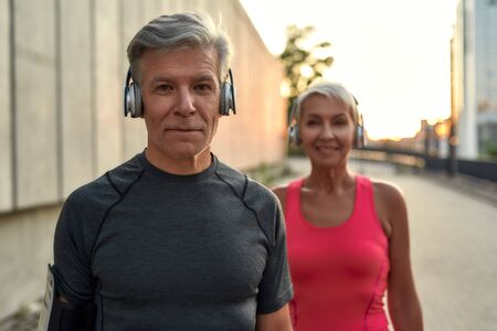 Portrait of happy and beautiful middle-aged couple in headphones looking at camera with smile while training together outdoors Stockfoto