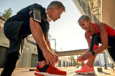 Preparing to run. Active and healthy middle-aged couple in sports clothing tying shoelaces before jogging outdoors