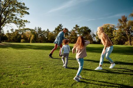 Full-length portrait of happy mother, father, little boy and girl running and playing catch game in autumn park. Family, parenthood, leisure and people concept. Horizontal shot. Reklamní fotografie