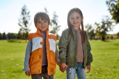 Happy together. Portrait of cute brother and sister holding hands and looking at camera with smile while standing in the park Foto de archivo