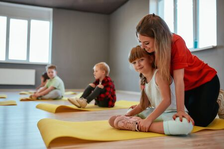 Cute little girl doing butterfly exercise with female trainer and smiling at camera. Group of children sitting on the floor and doing gymnastic exercises in the dance studio