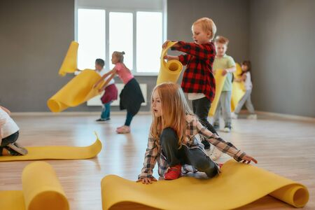 Gymnastic lesson. Group of cute children in casual clothes putting yellow mats on the floor and preparing for yoga class in the dance studio