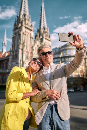 Traveling together. Happy middle-aged caucasian couple in sunglasses taking selfie by mobile phone and smiling while standing against beautiful catholic church