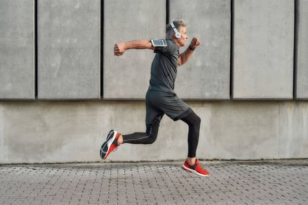 No limits. Active middle aged man in sport clothing jumping while exercising outdoors