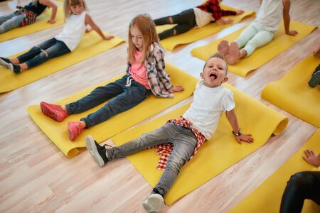 Making funny face. Close up portrait of cute boy sitting on the yellow yoga mat and sticking out his tongue while having a yoga class in the dance studio