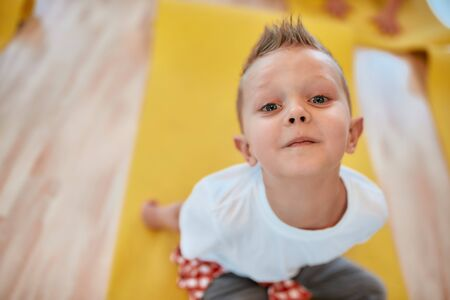 So cute. Portrait of a happy little boy in white t-shirt sitting on the yoga mat and smiling at camera while having a yoga class in the dance studio
