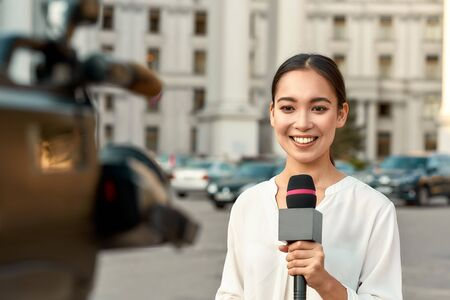 TV reporter presenting the news outdoors. Journalism industry, live streaming concept.