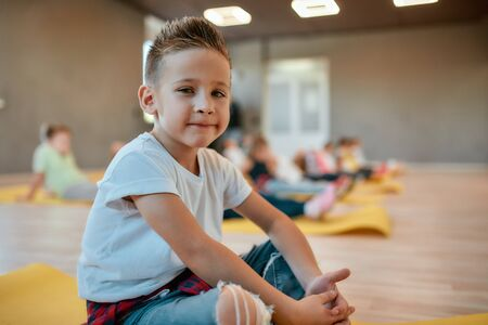 Portrait of a cute little boy in white t-shirt sitting on the yoga mat and smiling at camera while having a yoga class in the dance studio