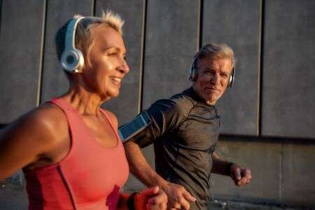 Be healthy. Sporty and happy middle-aged couple in headphones running together through the city street in the morning Zdjęcie Seryjne