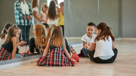 Relaxation time. Back view of fashionable kids talking with each other while sitting on the floor and having a break in the dance studio. Choreography class