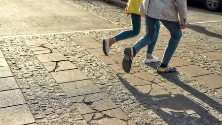 We should be there in time. Cropped photo of a couple in casual clothes running across the street. Walking together. Web banner. Crosswalk Reklamní fotografie