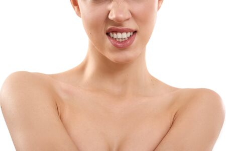 Showing her teeth. Cropped photo of young half-naked blond woman with short hair snarling at the camera while standing against white background