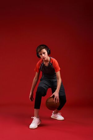 Take it to the Net. A teenage boy is engaged in sport, looking at camera while exercising with basketball. Isolated on red background. Fitness, training, active lifestyle concept. Vertical shot.