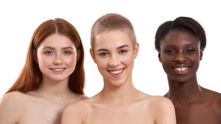 Natural Beauty. Three cheerful multicultural young women looking at camera and smiling while standing against white background. Beautiful models with black, red and blonde hair standing in row