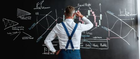 Build your real worth. Rear view of middle-aged employee, trader standing near blackboard full of charts, while thinking of the new strategy of work. Horizontal shot Imagens