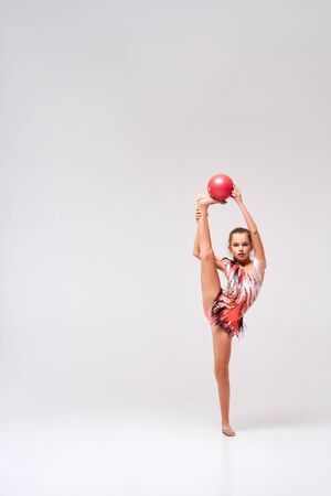 Keep balance. Full-length shot of flexible cute girl child gymnast doing acrobatic exercise using ball isolated on a white background. Sport, training, rhythmic gymnastics concept 写真素材