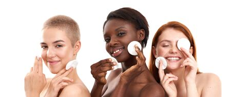 All people need skincare. Three positive multicultural young women removing makeup from face with cotton pads and smiling while standing in studio against white background