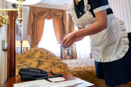 Our vision, our best service. Hotel maid in uniform putting welcome chocolate on the bed table in luxury hotel room. Room service concept. Archivio Fotografico