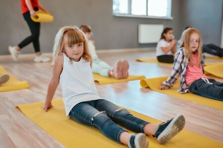 I love sport. Portrait of a pretty little girl sitting on the yellow yoga mat and looking at camera with smile while having a yoga class in the dance studio. Children doing gymnastic exercises Stok Fotoğraf