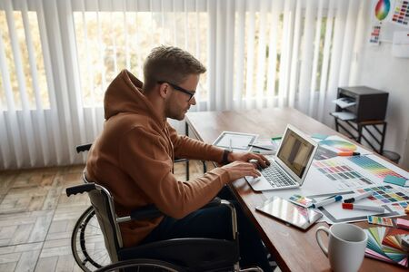 Creative professional. Side view of young male UX UI designer in a wheelchair designing new mobile app, working on laptop at his creative workplace in the modern office. User experience concept