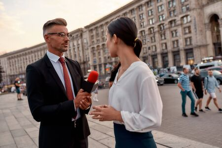 Professional reporter interviewing woman on urban street. Journalism industry, live streaming concept Stok Fotoğraf
