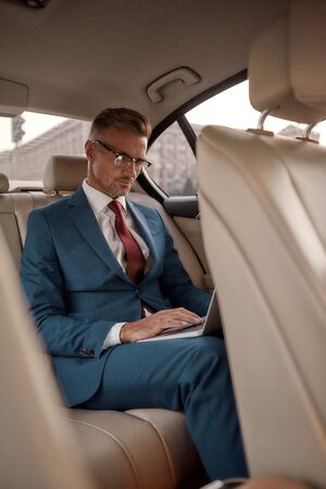 Never stop working. Serious mature businessman in full suit working on his laptop while sitting in the car