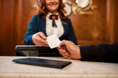 We invite you to try it. Close up of male and female hands. Smiling female receptionist behind counter in hotel giving key card to the guest.