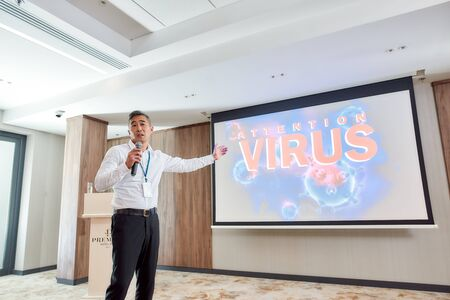 Attention. Asian male speaker in suit with headset and laser pointer giving a talk at corporate business meeting with the theme of coronavirus Standard-Bild