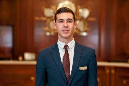 Responsible administrator. Close up of happy male receptionist worker in uniform looking at camera with a smile while standing at hotel lobby