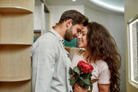 In love. Handsome caucasian man bringing flowers to his girlfriend. Happy couple hugging while standing indoors